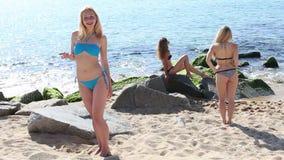 Traje de baño que lleva de la mujer que se coloca en la playa arenosa almacen de video