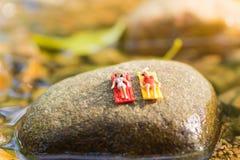 Traje de baño que lleva de la mujer miniatura que se relaja en la piedra de la cascada, usando como concepto del negocio del viaj Imagen de archivo