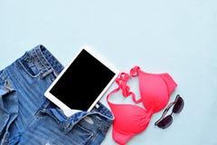 Traje de baño y accesorios femeninos del bikini del verano en azul con la tableta y las gafas de sol Fotografía de archivo