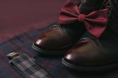 Traje de Borgoña de los hombres, corbata de lazo y zapatos de cuero del vintage en fondo del tweed de la materia textil Imagenes de archivo