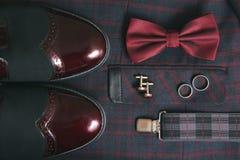 Traje de Borgoña de los hombres, corbata de lazo y zapatos de cuero del vintage en fondo del tweed de la materia textil Foto de archivo