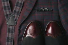 Traje de Borgoña de los hombres, corbata de lazo y zapatos de cuero del vintage en fondo del tweed de la materia textil Imagen de archivo