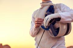 Traje de cercado blanco que lleva del cercador y sostener su máscara de cercado y una espada en fondo soleado Fotos de archivo libres de regalías