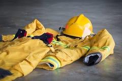 Traje de la protección del bombero y recurso seguro del casco en la tierra en el sta del fuego fotos de archivo