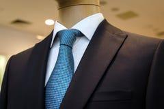 Traje de negocios negro con una camisa blanca y con un lazo azul en el dibujo Foto de archivo