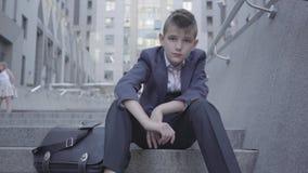 Traje de negocios que lleva del muchacho lindo pensativo que se sienta en las escaleras en la calle El muchacho está cansado y qu almacen de metraje de vídeo