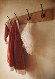 Traje de Santa que cuelga en el estante de la capa Foto de archivo libre de regalías