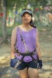 Traje del arnés de seguridad del adolescente que lleva asiático que se prepara para jugar Imagen de archivo