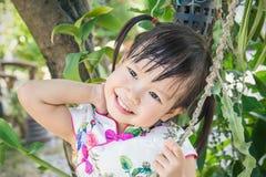 Traje del chino de la pequeña muchacha que lleva asiática linda en el parque Imágenes de archivo libres de regalías
