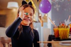 Traje del gato de la muchacha que lleva oscuro-cabelluda alegre que sonríe ampliamente sosteniendo el ojo gomoso foto de archivo libre de regalías