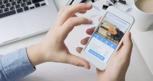 Traje del hotel de la reservación del hombre usando su smartphone y reservación en línea app móvil que se sientan en su escritori metrajes