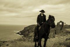 Traje del siglo XVIII hermoso de Rider Regency Poldark del caballo masculino con ruinas de la mina de lata y Océano Atlántico en  foto de archivo libre de regalías