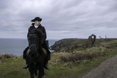 Traje del siglo XVIII hermoso de Rider Regency Poldark del caballo masculino con ruinas de la mina de lata y Océano Atlántico en  fotos de archivo