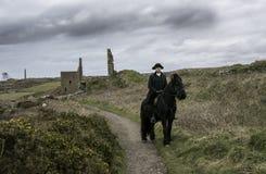 Traje do século XVIII considerável de Rider Regency Poldark do cavalo masculino com ruínas da mina de lata e campo no fundo imagem de stock