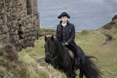 Traje do século XVIII considerável de Rider Regency Poldark do cavalo masculino com ruínas da mina de lata e Oceano Atlântico no  fotos de stock royalty free