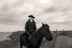Traje do século XVIII considerável de Rider Regency Poldark do cavalo masculino com ruínas da mina de lata e Oceano Atlântico no  imagens de stock royalty free