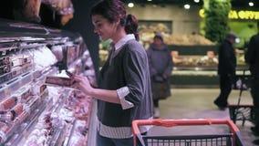 Traje fêmea moreno novo que olha o telefone celular ao andar através do corredor da carne na mercearia A menina toma o salame filme