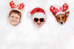 Traje lindo de los amigos en un reno y un sombrero de Papá Noel que mienten en nieve Foto de archivo libre de regalías