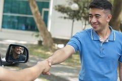Traje o amigo masculino atractivo que sacude la mano del conductor en día soleado imagen de archivo