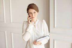 Traje que lleva de la mujer de negocios de la foto, mirando smartphone y llevando a cabo documentos en manos foto de archivo