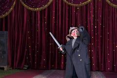 Traje vestindo do menino que guarda a espada na fase Fotos de Stock Royalty Free