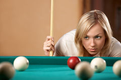 Trajectory calculation. The beautiful blonde aims in the course of game at billiards Royalty Free Stock Images