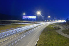 The trajectory of the road intersection at night. Car lights on a highway and transmission tower at night, long exposure photo of traffic Stock Photography