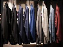 Trajes de los hombres en una tienda de la moda Imagen de archivo libre de regalías