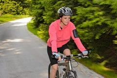 Trajeto biking do ciclismo do borrão de movimento da montanha da mulher imagem de stock royalty free