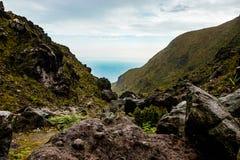 Trajeto da passagem do vale da montanha rochosa entre montanhas indonésias com o céu cinzento nebuloso Fotografia de Stock Royalty Free