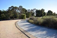Trajeto de madeira através do parque e das pastagem em um dia de verão ensolarado Imagens de Stock