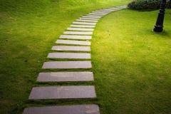 Trajeto de pedra de dobra do jardim na noite com incandescência claro da luz exterior do jardim Fotografia de Stock Royalty Free