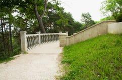Trajeto de pedra e trilhos do parque cercados por árvores e por grama foto de stock royalty free