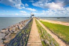 Trajeto de pedra que conduz ao farol na costa de mar Foto de Stock Royalty Free