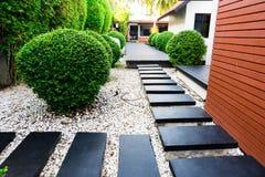 Trajeto do jardim nos seixos brancos e em árvores verdes luxúrias Fotografia de Stock Royalty Free