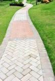 Trajeto do tijolo da curva no jardim Fotos de Stock Royalty Free