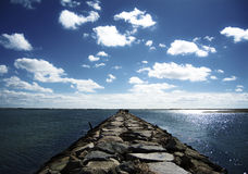 Trajeto longo da rocha através do oceano Fotos de Stock Royalty Free