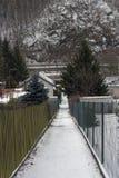 Trajeto nevado estreito entre as cercas e as casas de campo que conduzem para baixo fotos de stock royalty free