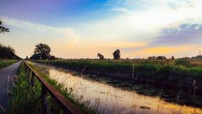 Trajeto vazio do ciclismo ao longo do Naviglio Pavese, canal no por do sol O canal estica para 30km de Pavia a Milão em Lombardy, Imagem de Stock