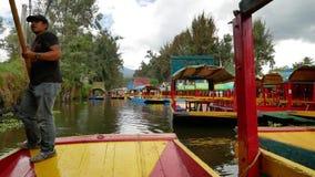 Trajinero row the trajinera in Xochimilco, Mexico stock footage