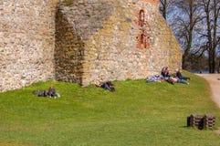 Trakai, Litouwen, 30-04-2017 De mensen liggen op het gras en zonnebaden in de de lentezon dichtbij de muren van het oude kasteel  stock afbeeldingen