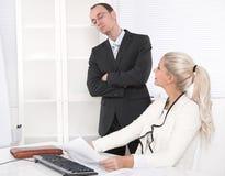 Trakassera: framstickande som kontrollerar hans sekreterare. Arkivfoton