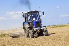 Traktor arbeitet auf dem Gebiet Stockbild