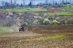 Traktor auf dem Feld, das an Land arbeitet Stockfotografie
