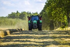 Traktor auf dem Feld während der Erntezeit an einem sonnigen Tag stockfoto
