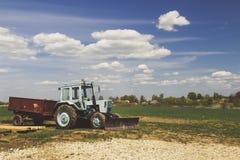Traktor auf dem Gebiet mit blauem Himmel und Wolken Stockbild