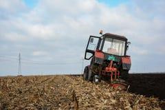 Traktor auf dem Gebiet mitten in Ackerbau Lizenzfreies Stockfoto
