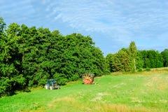 Traktor auf dem grünen landwirtschaftlichen Feld auf dem Hintergrund des Waldgürtels und des blauen bewölkten Himmels stockfotos