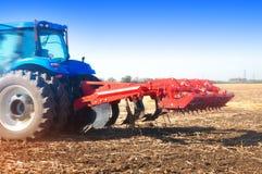 Traktor auf einem Gebiet, sonniger Tag des Herbstes Lizenzfreies Stockfoto