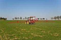 Traktor auf spritzender Plage des Feldes Lizenzfreie Stockfotos